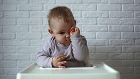 Den lilla gulliga pojken gnider hans ögon, medan sitta i barns stol lager videofilmer