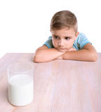 Den lilla gulliga pojken i en blå t-skjorta ser ett genomskinligt glass av smakligt mjölkar mycket stnding som isoleras på en vit arkivfoton