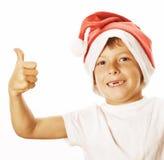 Den lilla gulliga pojken i santas den röda hatten isolerade tummar Arkivfoto