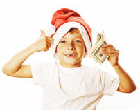 Den lilla gulliga pojken i santas den röda hatten som isoleras med den kontanta amerikanen gör Fotografering för Bildbyråer