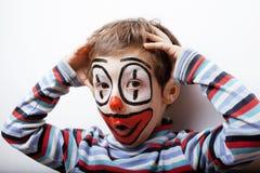 Den lilla gulliga pojken med facepaint som clown, pantomimic uttryck stänger sig upp Arkivbilder