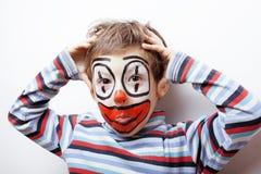 Den lilla gulliga pojken med facepaint som clown, pantomimic uttryck stänger sig upp Royaltyfria Bilder