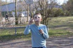 Den lilla gulliga pojken som blåser bubblor i, parkerar royaltyfria foton