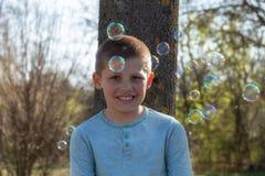Den lilla gulliga pojken som bl?ser bubblor i, parkerar arkivbild