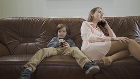 Den lilla gulliga pojken som sitter på, piskar soffan med ben som ändrar ifrån varandra kanaler på TV genom att använda äldre sys arkivfilmer