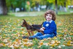 Den lilla gulliga pojken som spelar med hans hund i höst, parkerar royaltyfria bilder