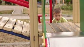 Den lilla gulliga pojken spelas på lekplatsen i den öppna luften, honom klättrar kullen arkivfilmer