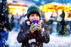 Den lilla gulliga ungepojken som dricker varma barn, stansar, eller choklad på tysk jul marknadsför Lyckligt barn på traditionell arkivbilder