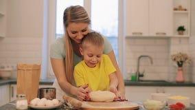 Den lilla härliga blonda pojken hjälper modern att laga mat Mamman och sonen i färgrika skjortor är rullar ut degen Mamman är stock video