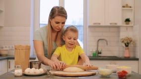 Den lilla härliga blonda pojken hjälper modern att laga mat Mamman och sonen i färgrika skjortor är rullar ut degen Mamman är lager videofilmer