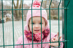 Den lilla härliga flickan behandla som ett barn bak staketet, det inlåsta rastret ett lock och ett omslag med ledsen sinnesrörels Arkivbilder
