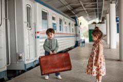 Den lilla härliga flickan i retro klänning säger farväl på stationen med lite pojken i tappningkläder med den retro resväskan fotografering för bildbyråer