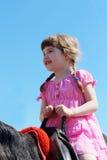 Den lilla härliga flickan i rosa färgklänning sitter på bruna hors Royaltyfria Foton