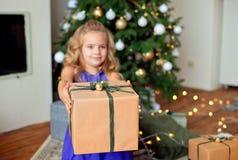 Den lilla härliga flickan med blont lockigt hår sträcker en julgåva mot bakgrunden av julgranen fotografering för bildbyråer