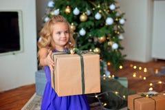 Den lilla härliga flickan med blont lockigt hår sträcker en julgåva mot bakgrunden av julgranen arkivbilder