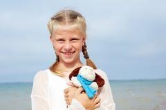 Den lilla härliga flickan omfamnar en underhållande hund-leksak arkivbilder