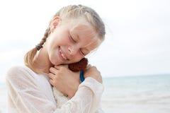 Den lilla härliga flickan omfamnar en underhållande hund - leksak Favorit- mjuk leksak arkivfoto
