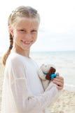 Den lilla härliga flickan omfamnar en underhållande hund - leksak Favorit- mjuk leksak arkivbild