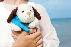 Den lilla härliga flickan omfamnar en underhållande hund - leksak Favorit- mjuk leksak royaltyfri fotografi