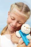 Den lilla härliga flickan omfamnar en underhållande hund - leksak Favorit- mjuk leksak arkivbilder