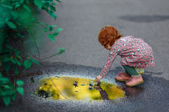 Den lilla härliga rödhåriga lilla flickan behandla som ett barn handlag pölen af royaltyfri fotografi