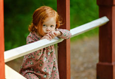 Den lilla härliga rödhåriga lilla flickan ser ledsen, i sommaren royaltyfri bild