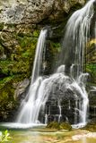 Den lilla härliga vattenfallet som faller över grå färger, vaggar royaltyfri foto