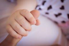 den lilla handen av ett nyfött behandla som ett barn arkivfoto