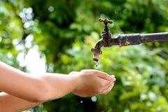 Den lilla handen väntar på vattendroppe från vattenkranen Fotografering för Bildbyråer