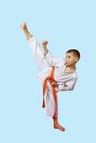 Den lilla idrottsmannen i en kimono utför en hög slagfot Arkivbilder