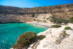 Den lilla isolerade golfen av Vathi, i Kreta, med den sandiga stranden och några lyckliga campare royaltyfri bild