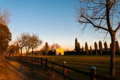 Den lilla italienska stadkyrkan på solnedgången i utomhus- parkerar i turistic fläck i höstafton Arkivbild