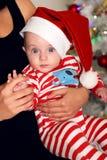 Den lilla jultomten behandla som ett barn att posera bredvid julgranen på slags tvåsittssoffahemmet med garnering för det nya åre Arkivbilder