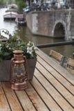 Den lilla kopparlyktan är på trätabellen med blommor Royaltyfria Foton