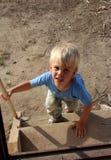 Den lilla landspojken med en smutsig framsida klättrar trappan royaltyfri bild