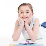 Den lilla le flickan ligger med boken Fotografering för Bildbyråer