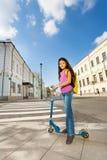 Den lilla le flickan står på sparkcykeln i staden Arkivfoton