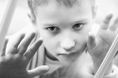 Den lilla ledsna pojken ser ut fönstret Svartvitt foto av ett närbildbarn Hungrigt barn med stora klara ögon som äter bröd royaltyfri foto