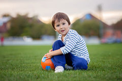 Den lilla litet barnpojken som spelar fotboll och fotboll och att ha gyckel, överträffar Arkivfoto
