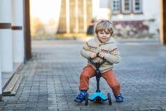 Den lilla litet barnpojkeridningen och hans sparkcykel cyklar i sommar Arkivbild