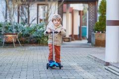 Den lilla litet barnpojkeridningen och hans sparkcykel cyklar i sommar Royaltyfria Bilder