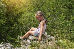 Den lilla ljusa flickan sitter på kanten av berget och ser in i avståndet på bergen fotografering för bildbyråer