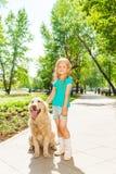 Den lilla lockiga blonda flickan med hunden i soligt parkerar Arkivfoton
