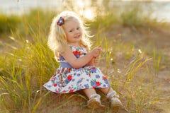 Den lilla lockiga blonda flickan sitter och ler på sand och gräs i su Arkivbild