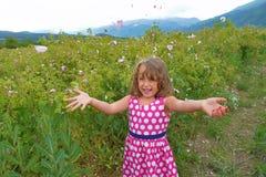Den lilla lyckliga flickan i dalen av rosor kastar kronblad royaltyfri bild