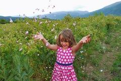 Den lilla lyckliga flickan i dalen av rosor kastar kronblad arkivfoton