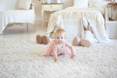 Den lilla lyckliga flickan i rosa färger klär beh för krypningen och för två leksakkaniner arkivbild
