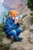 Den lilla lyckliga pojken dricker från en termos royaltyfri fotografi