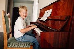 Den lilla lyckliga pojken spelar pianot royaltyfria foton
