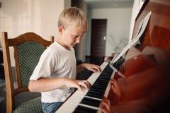 Den lilla lyckliga pojken spelar pianot arkivfoto